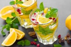 Cocktail de mojito de citron avec la menthe fraîche et la grenade, boisson régénératrice froide d'été ou boisson avec de la glace Photographie stock libre de droits