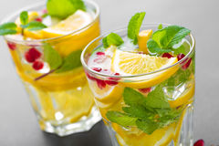 Cocktail de mojito de citron avec la menthe fraîche et la grenade, boisson régénératrice froide d'été ou boisson avec de la glace Images stock