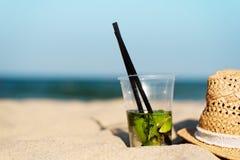 Cocktail de Mojito no chapéu da praia e de palha Fundo borrado da praia com espaço da cópia Sun, embaçamento do sol, brilho fotos de stock