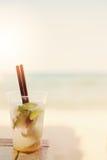 Cocktail de Mojito sur la plage, fond brouillé de plage Sun, brume du soleil, éclat photographie stock libre de droits