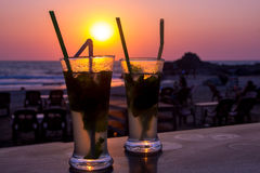 Cocktail de Mojito sur la plage, le coucher du soleil et la mer à l'arrière-plan Photographie stock libre de droits