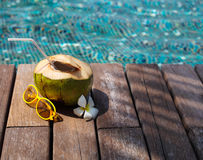 Cocktail de noix de coco avec la paille à boire par la piscine Photo stock