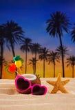 Cocktail de noix de coco sur les lunettes de soleil tropicales de coeur de plage de sable Images stock