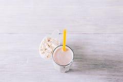 Cocktail de protéine avec une paille dans un verre et un scoop sur un OE blanc images stock