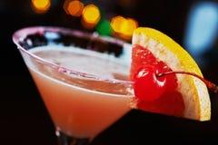 Cocktail de refrescamento brilhantes em uma tabela em um restaurante com a decoração criativa de fatias alaranjadas vermelhas em  Foto de Stock Royalty Free