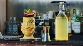 Cocktail de Tiki com fruto de paixão, jigger e uma garrafa com tintura na barra Foto de Stock Royalty Free
