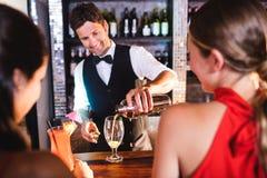 Cocktail de versement de barman en verre au compteur de barre photos libres de droits