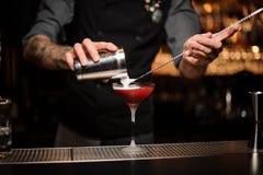 Cocktail de versement de barman utilisant le dispositif trembleur et la cuillère photo libre de droits