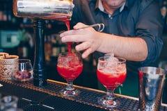 Cocktail de versement de rouge de cerise de barman utilisant la boisson juteuse d'esprit doux de tamis sur un compteur de barre V photo libre de droits