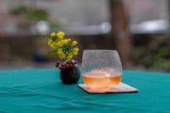 Cocktail dell'alcool in vetro con il piccolo vaso di fiore sulla tavola Fotografie Stock Libere da Diritti