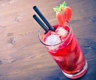 Cocktail della fragola con ghiaccio sulla vecchia tavola di legno, vecchio stile Immagine Stock