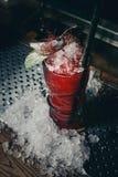 Cocktail della fragola con ghiaccio tritato su una pendenza rossa Immagini Stock