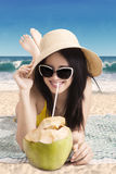 Cocktail della noce di cocco della bevanda della donna alla costa immagini stock