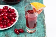 Cocktail della sangria di estate in piccolo vetro, piatto con le bacche del corniolo Fotografia Stock Libera da Diritti