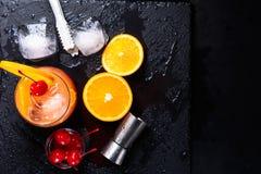 Cocktail di alba di tequila, arancia, cubetti di ghiaccio, ciliege di maraschino, tenaglie di ghiaccio e jigger su un vassoio ner Immagine Stock Libera da Diritti