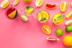 Cocktail di frutta tropicale con alcool Vetro con la bevanda vicino alle arance, al pompelmo, alla calce ed ai rosmarini su fondo Immagini Stock
