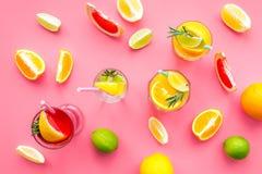 Cocktail di frutta tropicale con alcool Vetro con la bevanda vicino alle arance, al pompelmo, alla calce ed ai rosmarini su fondo Immagine Stock Libera da Diritti
