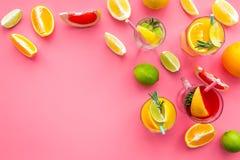 Cocktail di frutta tropicale con alcool Vetro con la bevanda vicino alle arance, al pompelmo, alla calce ed ai rosmarini su fondo Immagini Stock Libere da Diritti
