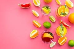 Cocktail di frutta tropicale con alcool Vetro con la bevanda vicino alle arance, al pompelmo, alla calce ed ai rosmarini su fondo Fotografia Stock