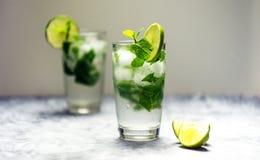 Cocktail di Mojito con calce e la menta in vetro su un fondo bianco Fotografia Stock Libera da Diritti