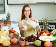 Cocktail di versamento del latte della donna felice con i frutti fotografia stock