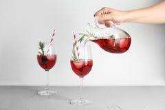 Cocktail di versamento del mirtillo rosso della donna nei glas immagine stock