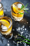 Cocktail do álcool com gelo e alecrins de fumo no limão escuro da tabela Fotografia de Stock