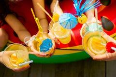 Cocktail do citrino do verão com os guarda-chuvas nas mãos das meninas Re Fotos de Stock Royalty Free