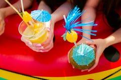Cocktail do citrino do verão com os guarda-chuvas nas mãos das meninas Re Imagens de Stock Royalty Free