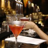 Cocktail Drink. Orange cocktail drink sitting on top of a bar with female hand in the background out of focus and a bar features. lemon slice in alcoholic Royalty Free Stock Photos