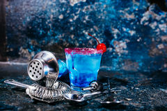 Cocktail drink with blue curacao and cherry served at bar Royalty Free Stock Photography