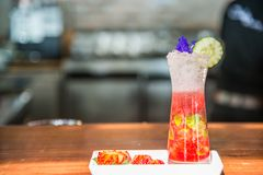Cocktail drink with piece of flower and cucumber on top. Cocktail drink with pieces of flower and cucumber on top and some sliced strawberry in white plate on Royalty Free Stock Images