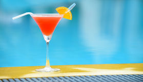Cocktail at the edge of the swimming pool Stock Images