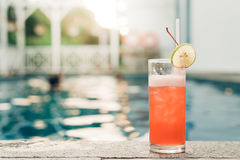 Cocktail at the edge of the swimming pool. Red cocktail with an orange slice on the background of the swimming pool. Stock Images