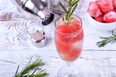 Cocktail efervescente com bolas da melancia e alecrins em um vidro do champanhe fotos de stock