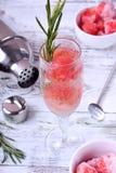 Cocktail efervescente com bolas da melancia e alecrins em um vidro do champanhe imagem de stock