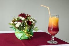 Cocktail en bloemboeket op de lijst stock foto