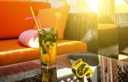 Cocktail exótico e óculos de sol amarelos à moda nos raios do sol Bebidas frias do álcool do verão fresco Grécia, Europa fotografia de stock