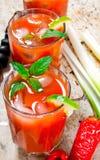 Cocktail fatti dei pomodori, della vodka, del ghiaccio, della calce, del pepe, del sale e dello spuntino con sedano ed olive nere immagini stock libere da diritti