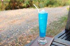 Cocktail frais avec le bleu placé sur une table en bois Photos stock