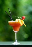 Cocktail freezer. Orange icy cocktail with blurry green background, beautifully arranged with pieces of freshly cut orange and a strawberry, in a tall glass Stock Photo
