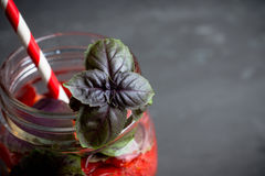Cocktail fresco con la fragola e basilico in vetro Immagine Stock