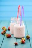 Cocktail fresco do leite da morango em uns frascos de pedreiro com palhas no azul Fotografia de Stock Royalty Free