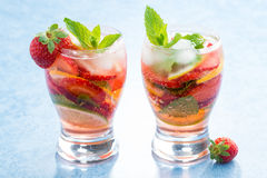 Cocktail with fresh strawberries and citrus in glasses Stock Images