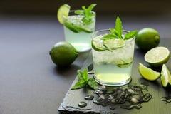 Cocktail frio com licor do limão, cal, tônico, gelo no fundo escuro Fotos de Stock Royalty Free