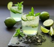 Cocktail frio com licor do limão, cal, tônico, gelo no fundo escuro Fotografia de Stock
