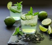 Cocktail frio com licor do limão, cal, tônico, gelo no fundo escuro Fotos de Stock