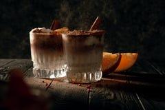 Cocktail frio polvilhado com a canela em um fundo escuro Baixa fotografia chave imagens de stock royalty free