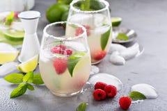 Cocktail froid d'été avec les chaux et la framboise Images libres de droits