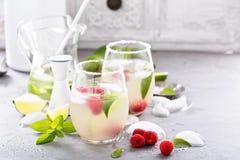 Cocktail froid d'été avec les chaux et la framboise Image stock